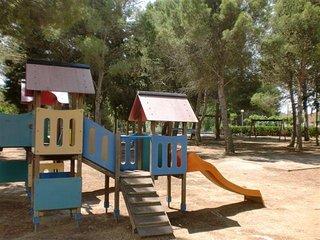 Parque infantil, al lado la piscina, enfrente de la casa.