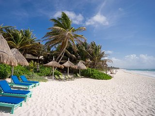 Tulum Beach in front of Casa Mandala with private loungers and shade palapas.