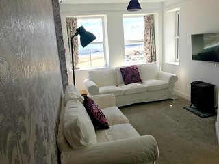 Lounge with bay window, offering panoramic sea views