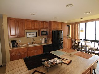 Open fully equipped kitchen to dining and living areas.
