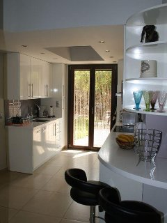 Another view of the kitchen and doors leading out to pool area and gardens