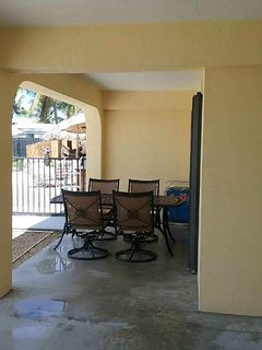 Rear cov'd patio: table, 4 swivel + 4 plastic chairs + NIP 4 NEW chaise loungers w 2 side tables...