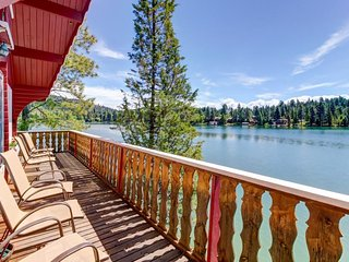 Cozy lakefront log cabin w/ lake views, a wood stove, vintage decor, & dock.