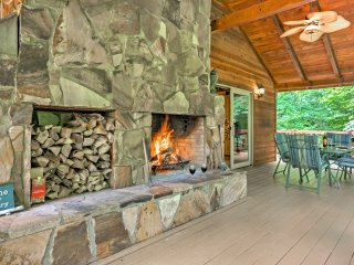 The home features an upper deck with a stone fireplace and patio furniture.