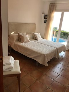 Twin bedroom with spacious fitted wardrobes and French doors on to pool and terrace.