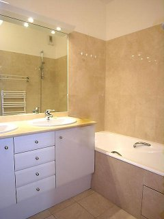 Bathroom 1: is equipped with : 2 washbasins, bathtub, built-in wall closet, tiled floor.