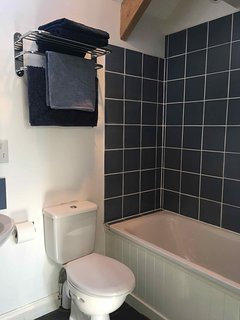Bathroom with shower over the bath, sink and toilet