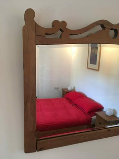 Carved wooden mirror in the double bedroom