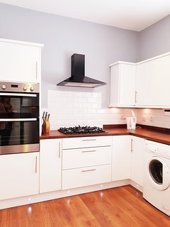 Modern fully fitted kitchen with double oven, gas hob, dishwasher and fridge freezer