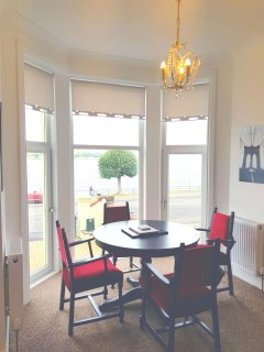 Dining area in sitting room with stunning sea views from floor to ceiling bay window