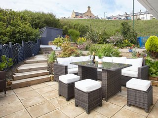 The garden and patio provide the perfect space for entertaining and taking in those seaside views