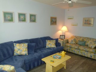 Warm and inviting with cozy beach decor and yellow sofa sleeper.