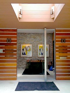 The door opens to an art filled stone foyer with guest closets.
