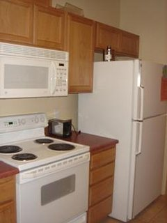 Kitchen featuring electric stove, refrigerator  microwave