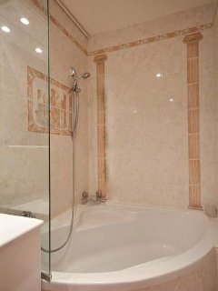 Bathroom 2 is equipped with : washbasin, bathtub with showerhead, toilet, built-in shelves, tiled fl