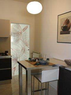 Cucina abitabile e completamente attrezzata con tavolo da colazione e accesso a terrazza di servizio