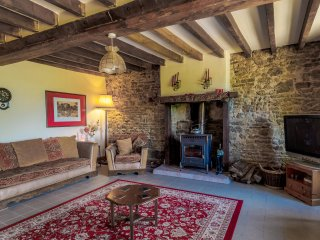 Spacious lounge to relax in, with traditional beamed ceiling and rustic features.
