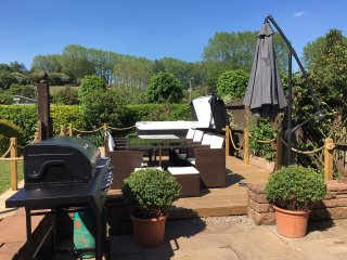 Decking area with hot tub, dining table and chairs and gas BBQ