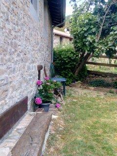 Banco de piedra y madera en el jardín pequeño