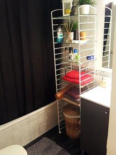 Lavabo con bañera, agua caliente y secador de pelo.