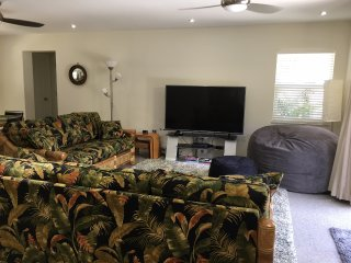 Lounge with comfortable seating, 65' UHDTV and French doors to pool and spa