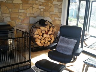 Sit back on the leather reclining lounge with a book in front of the wood fire.