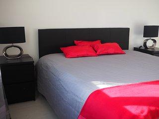 Chambre noire avec vue mer, un grand lit de 160 et un placard.