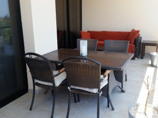 Large balcony with dining table, sofa and coffee table for al fresco relaxing.