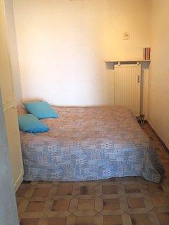 La chambre contient une penderie, une étagère et une table de nuit