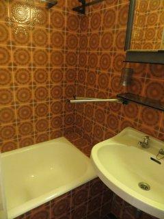 Le bain/douche assis de la salle de bain