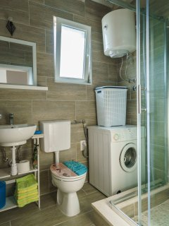 Bathroom with shower and laundry machine