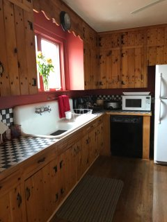 Kitchen has original high backed sink and pine cabinets.