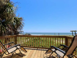 Watch pelicans soar above the beach from the screened porch of this elevated bea