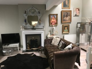 The main living room has velvet sofas and chairs, fur throws and lots of original art.