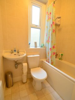 Bathroom with electric shower and bath