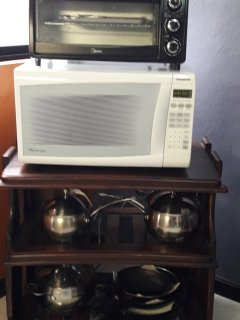 Microwave, toaster oven, skillets, and pots/pans.