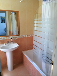 Bathroom with bath & power shower overhead