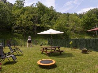 Amplio jardín cerrado con barbacoa y mesa de picnic.