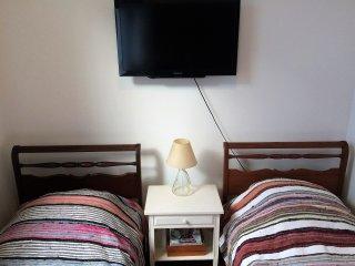 Quarto com duas camas de solteiro, área e banheiro privativo