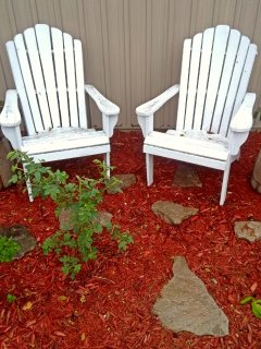 Muskoka chairs in the garden in front of your room. June 2017.
