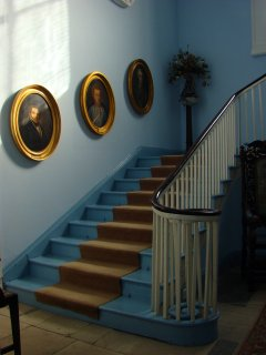 The airy stairwell with ancestral portraits