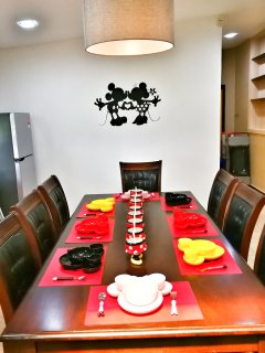 Dining area with Mickey plates, bowls, mugs, forks and spoons