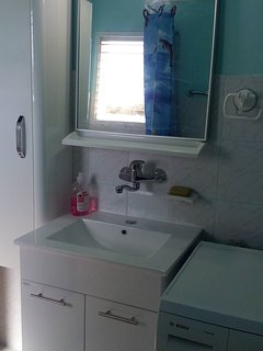 Newly renovated bathroom with bath and washing machine