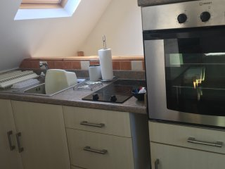Small Kitchen area, with essentials, microwave, fridge, oven, hob, crockery, cutlery, pans.