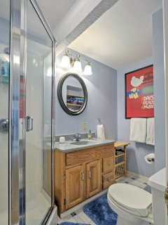 The full bathroom features a walk in shower.