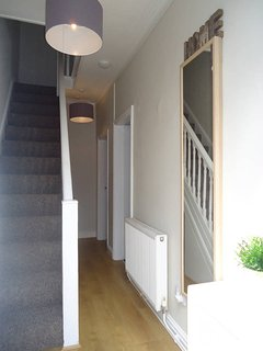 You step into a clean and bright corridor upon entry to the property.