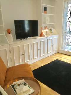Fitted cabinet holds large flat screen TV.