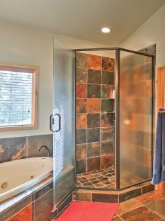 The private bath features a jacuzzi tub, his and hers sinks, and walk-in shower.