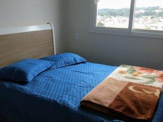 Quarto com cama de casal em apartamento. Com garagem e cafe da manha.