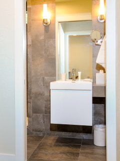 Lovely Bathroom with shampoo, conditioner, soap, makeup removers, hairdryer, too many items to list
